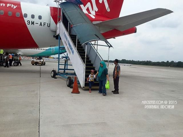 Hazeeq stepping out of the plane like a child star